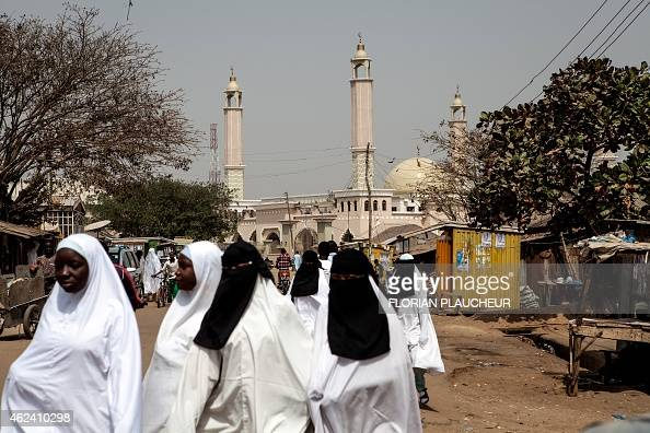 Muslim women walk past a Mosque in Kaduna on January 21 2015 All that's left of the Muslim neighbourhood in Madakiya in Nigeria's northwestern Kaduna...