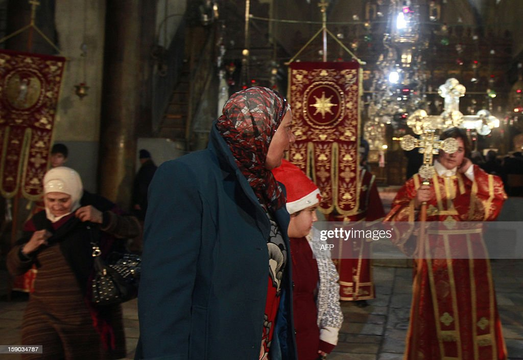 Muslim women watch as Greek Orthodox clergy wait for the arrival of Patriarch of Jerusalem Theophilos III to the Church of the Nativity in the biblical West Bank town of Bethlehem to attend Orthodox Christmas celebrations which kicked off on January 6, 2013, in the traditional birthplace of Jesus Christ.
