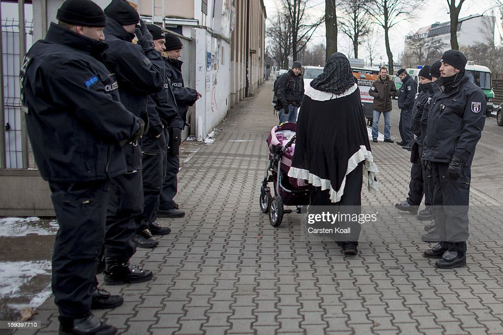 Muslim women wearing headscarves walk past police outside a building where Salafite supporters were meeting on January 13, 2013 in Berlin, Germany. The Salafites had originally planned to hold a public gathering in the city center to raise money for Muslims in Syria which included prominent speakers such as radical Islamic preacher Pierre Vogel. They then moved the event to a private gathering in Neukoelln district. Salafites are an ultra-conservative group of Muslim Sunnis with hundreds of members in Berlin and the area around Bonn and Cologne. German authorities are keeping a close eye on the group, especially since clashes that broke out last year in which Salafite demonstrators attacked police and right-wing counter-demonstrators.