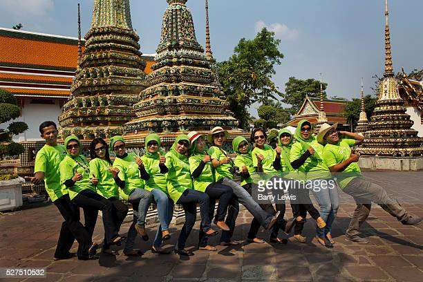Muslim workers from an insurance company all dressed in branded Tshirts pose for a group shot inside the temple of Wat Pho in Bangkok Thailand