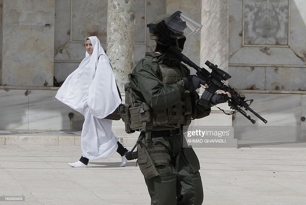 A Muslim worshiper walks past an Israeli riot policeman keeping position during clashes with Palestinian demonstrators at Jerusalem's al-Aqsa mosque compound following Friday prayers on March 8, 2013. Palestinians enraged by reports that an Israeli policeman mishandled a Koran battled riot officers at Jerusalem's Al-Aqsa mosque compound with stones and petrol bombs, police and witnesses said. AFP PHOTO/AHMAD GHARABLI