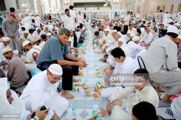 Muslim worshippers break the fast with a dinner distributed at the Prophet Mohammed Mosque during the Muslim holy fasting month of Ramadan on June 10...
