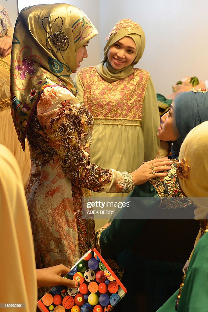Muslimah World pageant contestant Dayangku Rabiatul Adawiyah (L) of Brunei talks to other contestants while they prepare backstage for the grand final of the contest in Jakarta on September 18, 2013. The finale of a beauty pageant exclusively for Muslim women will take place in the Indonesian capital on September 18, in a riposte to the Miss World contest in Bali that has drawn fierce opposition from Islamic radicals.