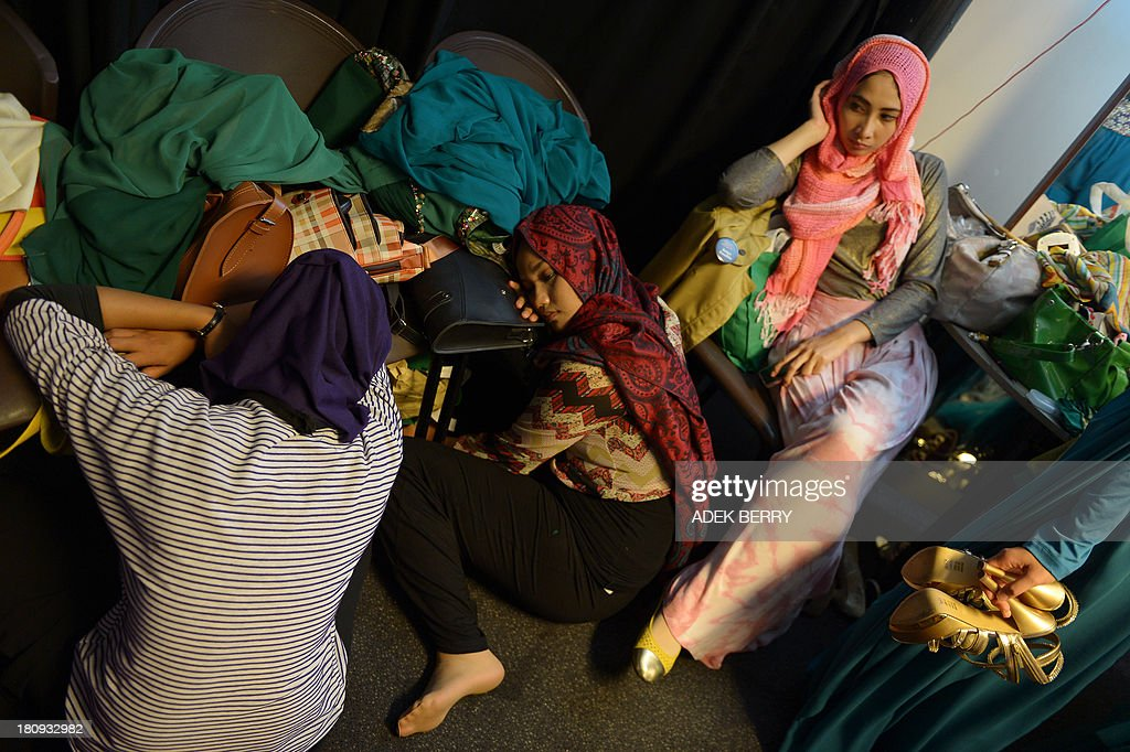 Muslimah World pageant contestant Futri Virginia (R) looks on while others rest as they prepare for the grand final of the Muslimah World at the back stage in Jakarta on September 18, 2013. The finale of a beauty pageant exclusively for Muslim women will take place in the Indonesian capital on September 18, in a riposte to the Miss World contest in Bali that has drawn fierce opposition from Islamic radicals.
