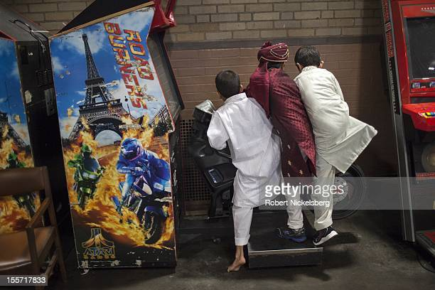 MuslimAmerican children play on a motorcycle video game October 26 2012 at the annual Eid alAdha prayer held at the Teaneck Armory in Teaneck New...