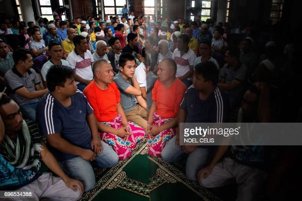 TOPSHOT Muslims are reflected on a marble wall as they pray during Friday prayers at a mosque in the vicinity of the Lanao Del Sur Capitol in Marawi...