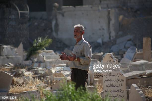 Muslims arrive to visit their relatives' damaged tombs after they performed Eid alFitr prayer at Jobar district of Damascus Syria on June 25 2017 Eid...