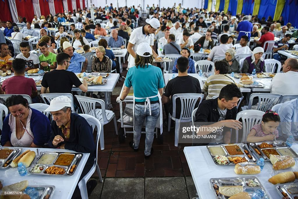 Muslims break the fast with a dinner distributed for free during the Muslim fasting month of Ramadan on June 29, 2016 in Pristina. Muslims fasting in the month of Ramadan must abstain from food, drink and sex from down to dusk, when they break the fast with meal known as iftar. / AFP / ARMEND