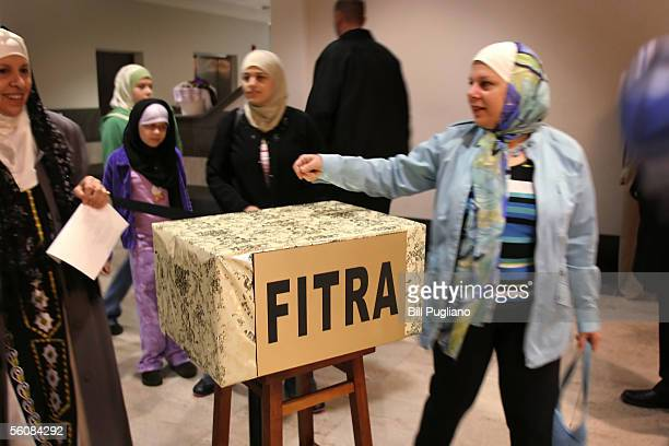 Muslims drop money into a special box at the Islamic Center of America during a celebration of Eid alFitr November 4 2005 in Dearborn Michigan The...