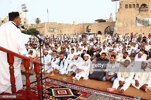 Muslims gather on Martyrs' Square to perform Eid alFitr prayer on the first day of Eid alFitr in Tripoli Libya on 28 July 2014