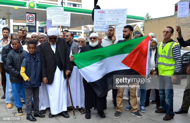 Muslims living in England wave Palestinian flag in solidarity with Gaza during a protest against a notice by HSBC bank to close the mosques bank...