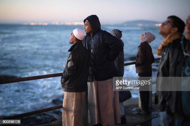 Muslims look out to sea after the evening prayer at Three Anchor Bay in Cape Town on June 24 as Islamic leaders attempt to sight the new moon which...