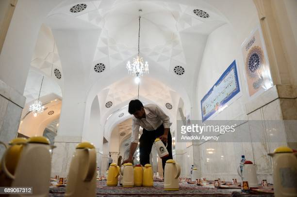 Muslims make preparations ahead of the Iftar dinner on the first day of the holy month of Ramadan at Shah Abdol Azim Shrine in Tehran Iran on May 27...