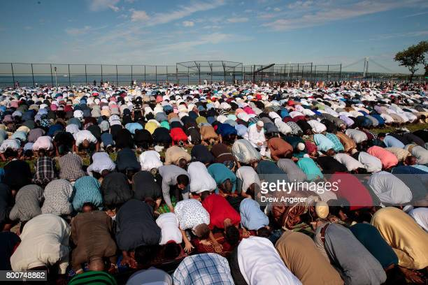 Muslims participate in a group prayer service during Eid alFitr which marks the end of the Muslim holy month of Ramadan in Bensonhurst Park in the...