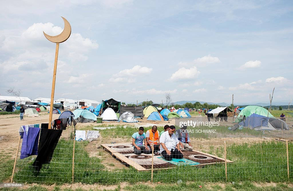 Muslims pray at a makeshift camp for migrants and refugees near the village of Idomeni not far from the Greek-Macedonian border on May 1, 2016. Some 54,000 people, many of them fleeing the war in Syria, have been stranded on Greek territory since the closure of the migrant route through the Balkans in February. / AFP / TOBIAS