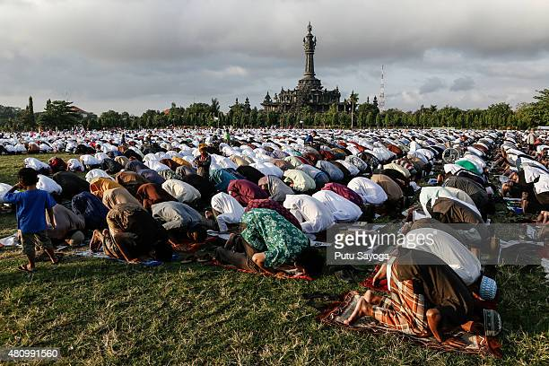 Muslims pray during mass to celebrate Eidul Fitr on July 17 2015 in Denpasar Bali Indonesia The twoday holiday Eid ulFitr marks the end of Ramadan...