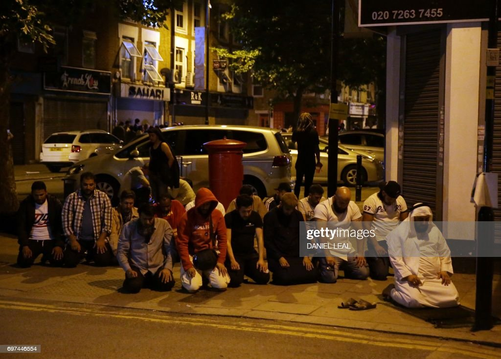 TOPSHOT - Muslims pray on a sidewalk in the Finsbury Park area of north London after a vehichle hit pedestrians, on June 19, 2017. One person has been arrested after a vehicle hit pedestrians in north London, injuring several people, police said Monday, as Muslim leaders said worshippers were mown down after leaving a mosque. / AFP PHOTO / Daniel LEAL