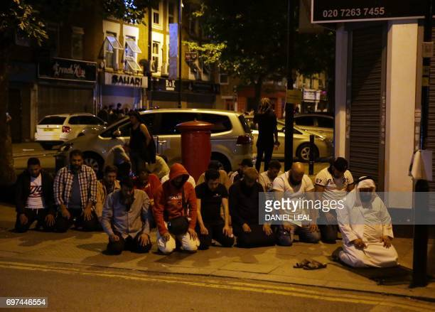 TOPSHOT Muslims pray on a sidewalk in the Finsbury Park area of north London after a vehichle hit pedestrians on June 19 2017 One person has been...