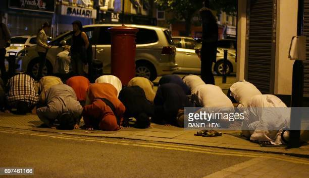 Muslims pray on a sidewalk in the Finsbury Park area of north London after a vehichle hit pedestrians on June 19 2017 One person has been arrested...