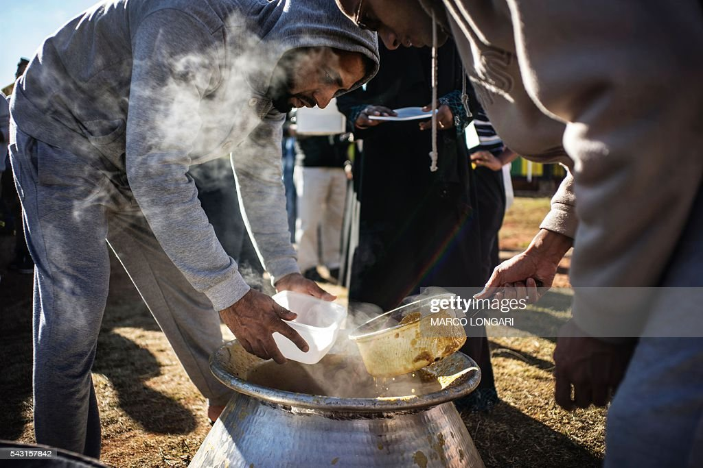 Muslims receive food before breaking the fast for Ramadan in Lenasia, on the outskirts of Johannesburg, on June 26, 2016. Muslims throughout the world are marking the month of Ramadan, the holiest month in the Islamic calendar, during which devotees fast from dawn until dusk. / AFP / MARCO