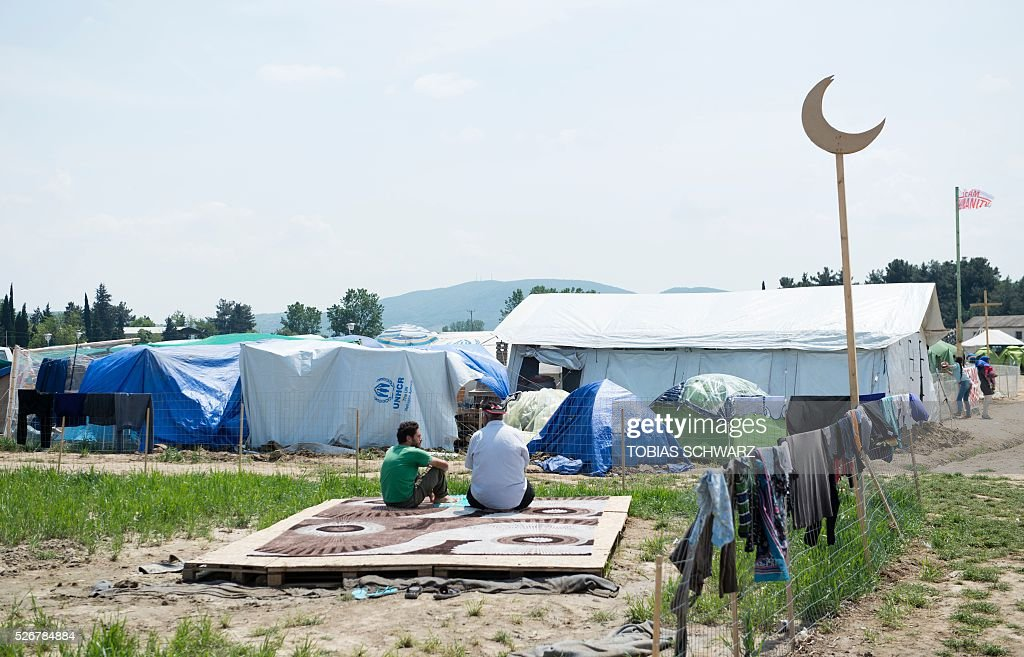 Muslims talk before praying at a makeshift camp for migrants and refugees near the village of Idomeni not far from the Greek-Macedonian border on May 1, 2016. Some 54,000 people, many of them fleeing the war in Syria, have been stranded on Greek territory since the closure of the migrant route through the Balkans in February. / AFP / TOBIAS