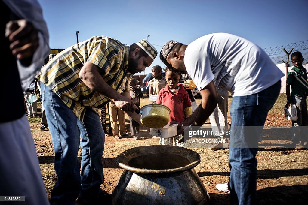 Muslims volunteers serve food before breaking the fast for Ramadan in Lenasia, on the outskirts of Johannesburg, on June 26, 2016. Muslims throughout the world are marking the month of Ramadan, the holiest month in the Islamic calendar, during which devotees fast from dawn until dusk. / AFP / MARCO
