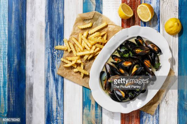 Mussels on white plate and french fries on wooden background copy space
