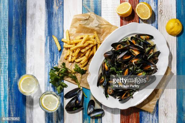 Mussels on white plate and french fries on wooden background