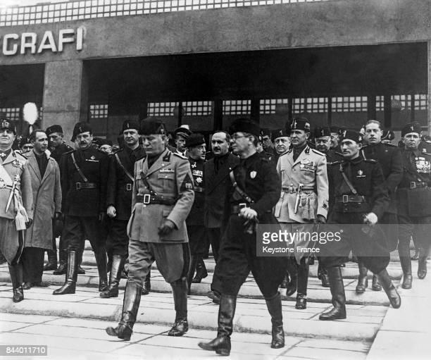 Mussolini accompagné de plusieurs personnalités du parti fasciste sort du nouvel hôtel des postes après l'inauguration à Rome Italie le 29 octobre...