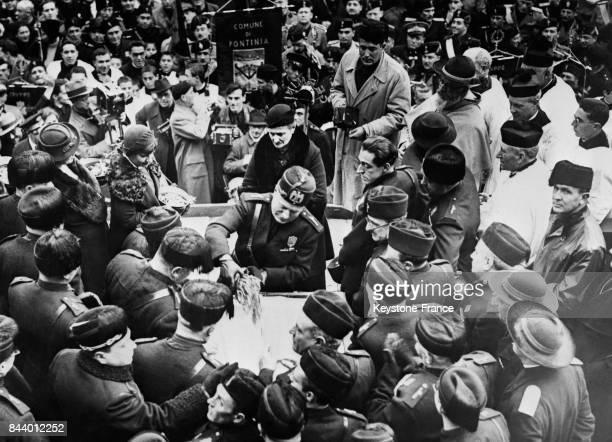 Mussolini verse dans une caisse les alliances en or offertes par les habitants à l'occasion de l'inauguration de la nouvelle ville de Pontinia Italie...