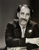 Mustache glasses and cigar never fail to identify Groucho Marx youngest member of the Marx Brothers who completed MGM's 'The Bargain Basement' their...