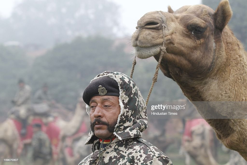 Mustached Jawan of BSF Camel corps with his camel during rehearsal for the Republic Day parade on a cold and foggy morning at Raisina Hill on January 7, 2013 in New Delhi, India. Dense fog and icy winds disrupted normal life as Delhi's minimum temperature settled at five notches below average at 2.4 degrees Celsius. Fog forced visibility to drop to about 500 metres in the morning resulting in 15 flights and 42 trains were delayed out of Delhi while 18 trains got cancelled.