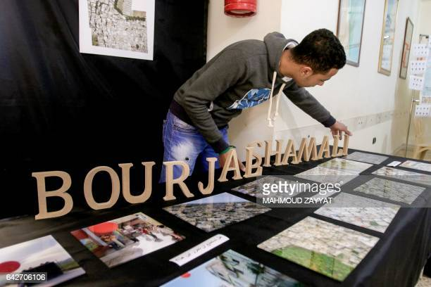 Mustafa Dakhlool a Palestinian refugee arranges letters spelling out the name of the Burj alShamali refugee camp next to aerial pictures of the site...