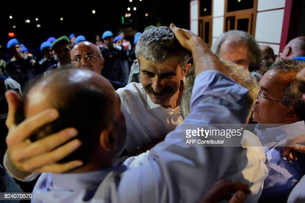 Mustafa Kemal Gungor a board member of the foundation that publishes the embattled opposition newspaper Cumhuriyet embraces a friend after being...