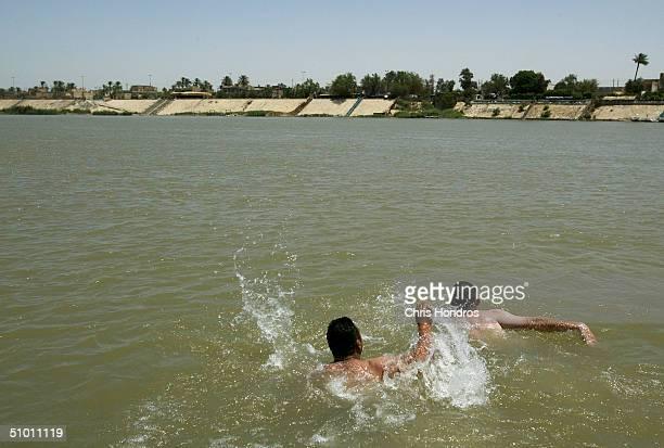 Mustaffa Muhammed Ali and La'ith Hassan Rashid swim in the Tigris river June 30 2004 in Baghdad Iraq Ali an enginnering student and Rashid a driver...