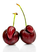 Two deformed cherries isolated on a white background.