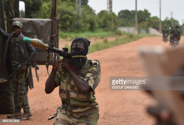 TOPSHOT A mutinous soldier holds a RPG rocket launcher inside a military camp in the Ivory Coast's central second city Bouake on May 15 2017 Gunshots...