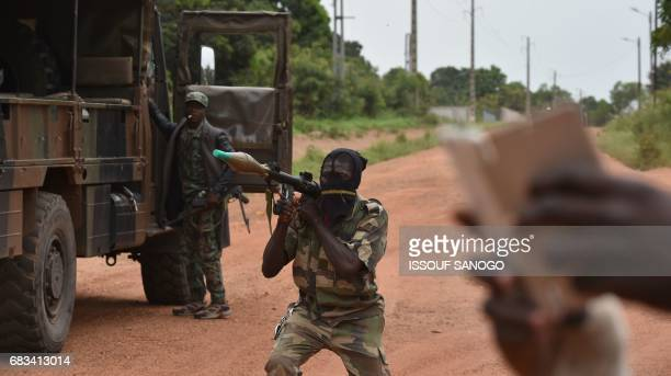 A mutinous soldier holds a RPG rocket launcher inside a military camp in the Ivory Coast's central second city Bouake on May 15 2017 Gunshots rang...