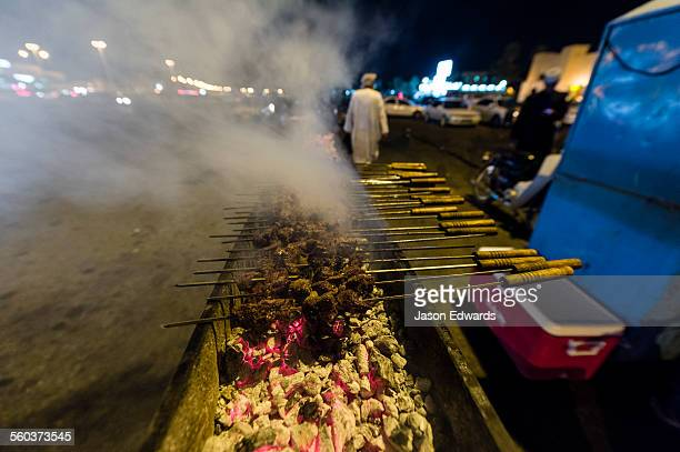 Smoke rises from meat kebabs grilling on hot coals in a night market.