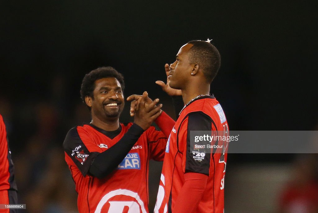 Muttiah Muralitharan congratulates Marlon Samuels of the Renegades after he took a wicket during the Big Bash League match between the Melbourne Renegades and the Adelaide Strikers at Etihad Stadium on January 2, 2013 in Melbourne, Australia.