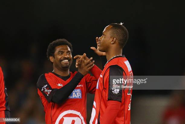 Muttiah Muralitharan congratulates Marlon Samuels of the Renegades after he took a wicket during the Big Bash League match between the Melbourne...