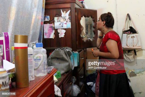 'Muxe' Biniza Carrillo sexual diversity activist applies makeup at her home in the Juchitan community in Oaxaca State Mexico on July 26 2017 Muxes...