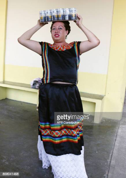 'Muxe' Biniza Carrillo sexual diversity activist carries a pack of beer on her head at the Juchitan community in Oaxaca State Mexico on July 26 2017...