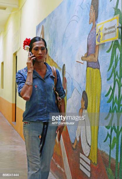 'Muxe' Estrella Vasquez uses his phone as she walks past a mural at the Juchitan community in Oaxaca State Mexico on July 26 2017 Muxes have been...