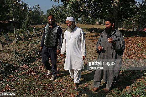 Muzaffar Wani father of rebel commander Burhan Wani looks at the grave of his son in Shareef Abad village in south Kashmirs Tral some 40 kilometers...