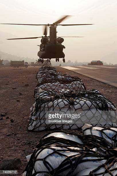 Muzaffarabad, Pakistan - Marine landing support specialists attached to the Combined Medical Relief team 3's helicopter Support Team, attach external loads, or sling loads, to the body of an Army CH-47 Chinook Cargo Helicopter, December 27.