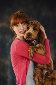 Woman posing with her pet dog in her arms.