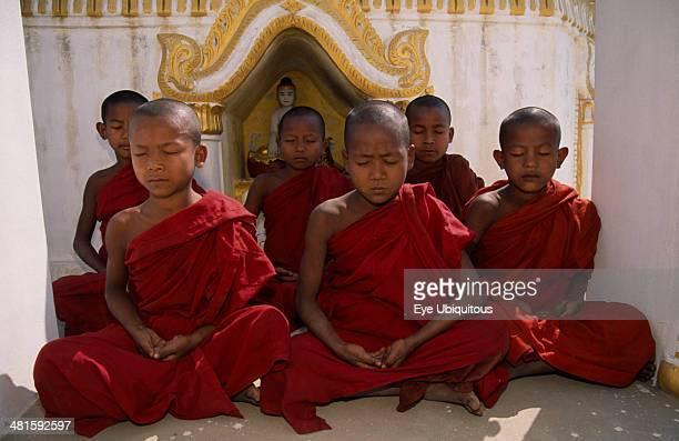 Myanmar Amarapura Young novice monks meditating in front of shrine near Mandalay