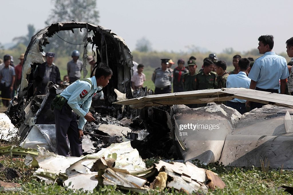 Myanmar army officials inspect the wreckage of a military passenger plane which crashed in a field near the airport in the capital of Naypyidaw on February 10, 2016. Four Myanmar military personnel were killed and one was seriously injured after the small air force propeller plane crashed shortly after take off in the capital Naypyidaw, officials said. AFP PHOTO / AFP / STR