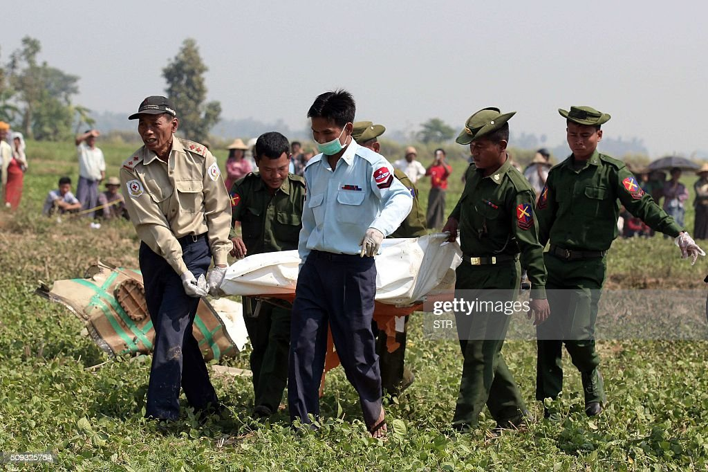 Myanmar army officials transport the body of a passenger who died when a military passenger plane crashed in a field near the airport in the capital of Naypyidaw on February 10, 2016. Four Myanmar military personnel were killed and one was seriously injured after the small air force propeller plane crashed shortly after take off in the capital Naypyidaw, officials said. AFP PHOTO / AFP / STR